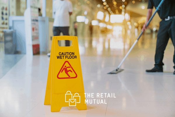 caution wet floor sign with person mopping in the background